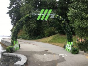 large truss arch covered in green wall greenery and custom plexglas signage for Vega promotional area at SeaWheeze