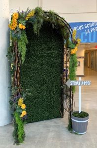 Artificial boxwood backdrop with whimsical wrought iron arch dressed in greenery and yellow flowers for photo opportunity at River Market