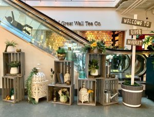 Elevator vignette featuring wood crates, vintage accessories, custom arrangements and signage at River Market escalator bank