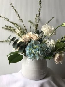 Rustic chick style ceramic container with eucalyptus, blue hydrangea and cream coloured roses for corporate event centres