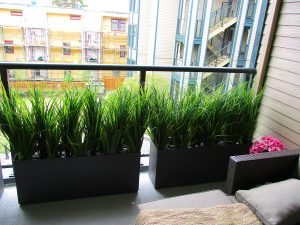 Artificial tall grass in aluminum planters for residential balcony decor and privacy