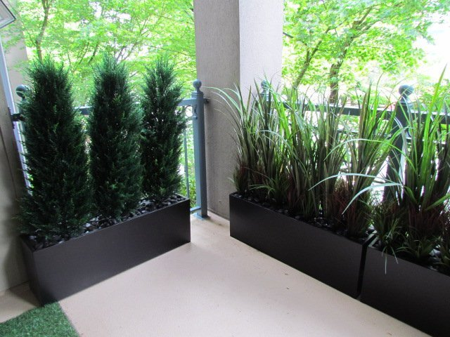 Condo balcony artificial greenery in low troughs, cedar topiary hedges and tall grass mix