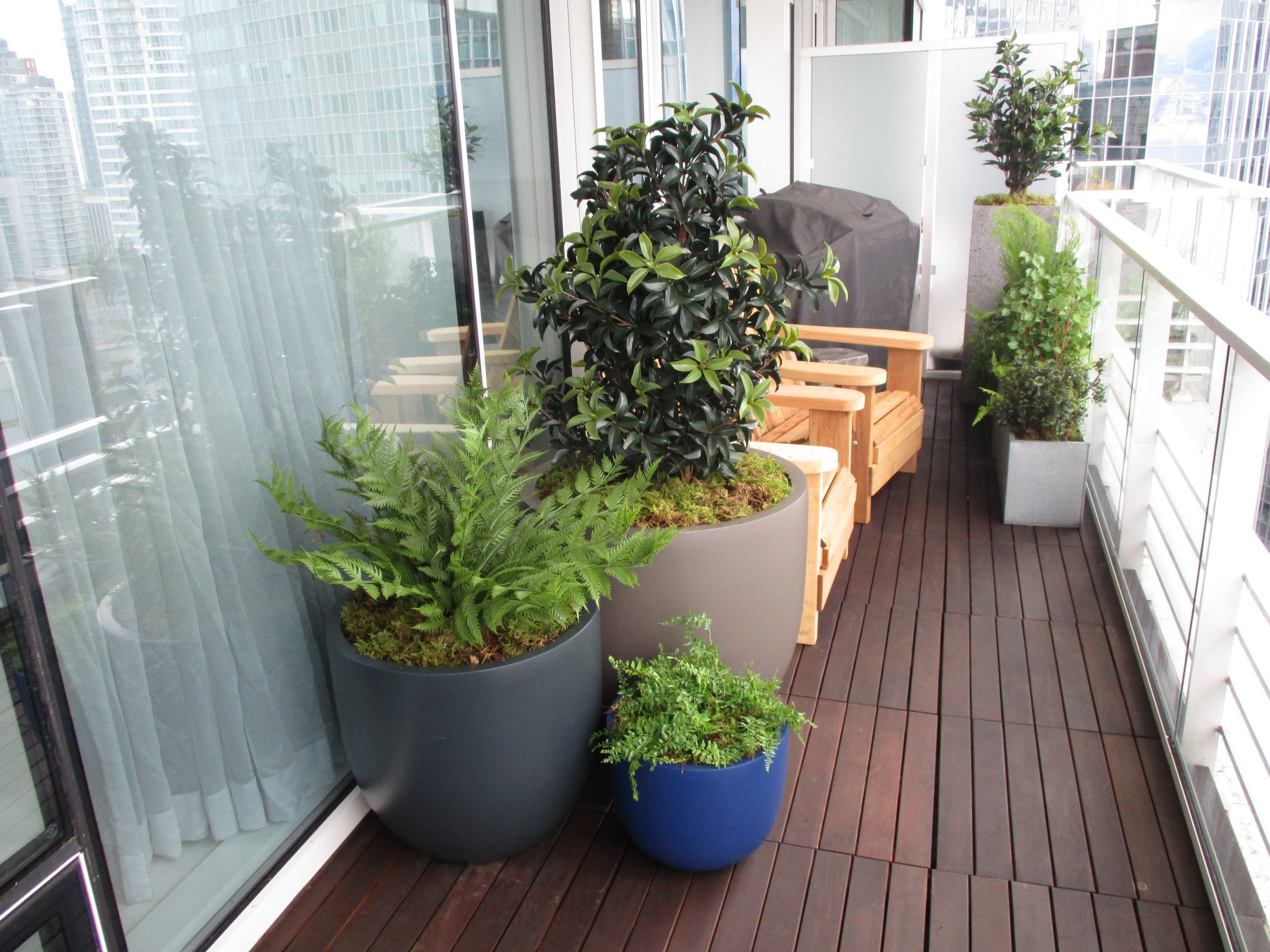 Artificial ferns, laurel and mixed west coast greenery in fibreglass round planter mix for residential patio
