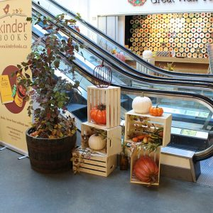 Fall themed display featuring wood crates, fall foliage and pumpkins