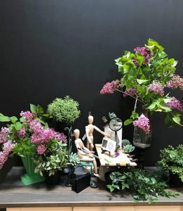 wide shot of mini collage of office space with desk and two maanniquins, artificial greenery and live purple flowers