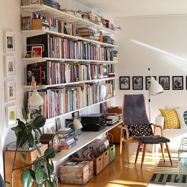 inspiration image of living room with full wall bookshelves and under counter storage