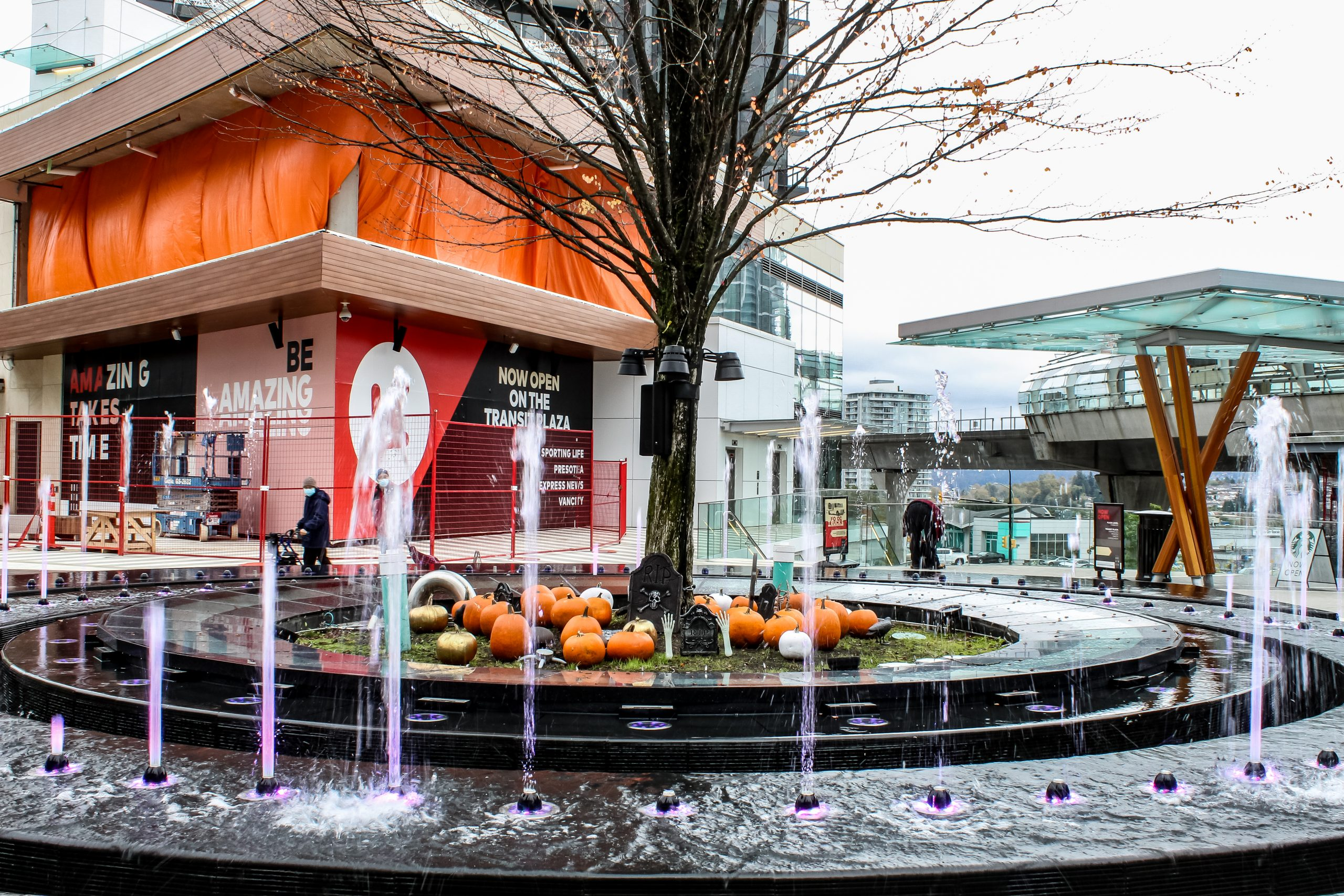 Giant outdoor fountain decorated with halloween pumpkins and fake graveyard
