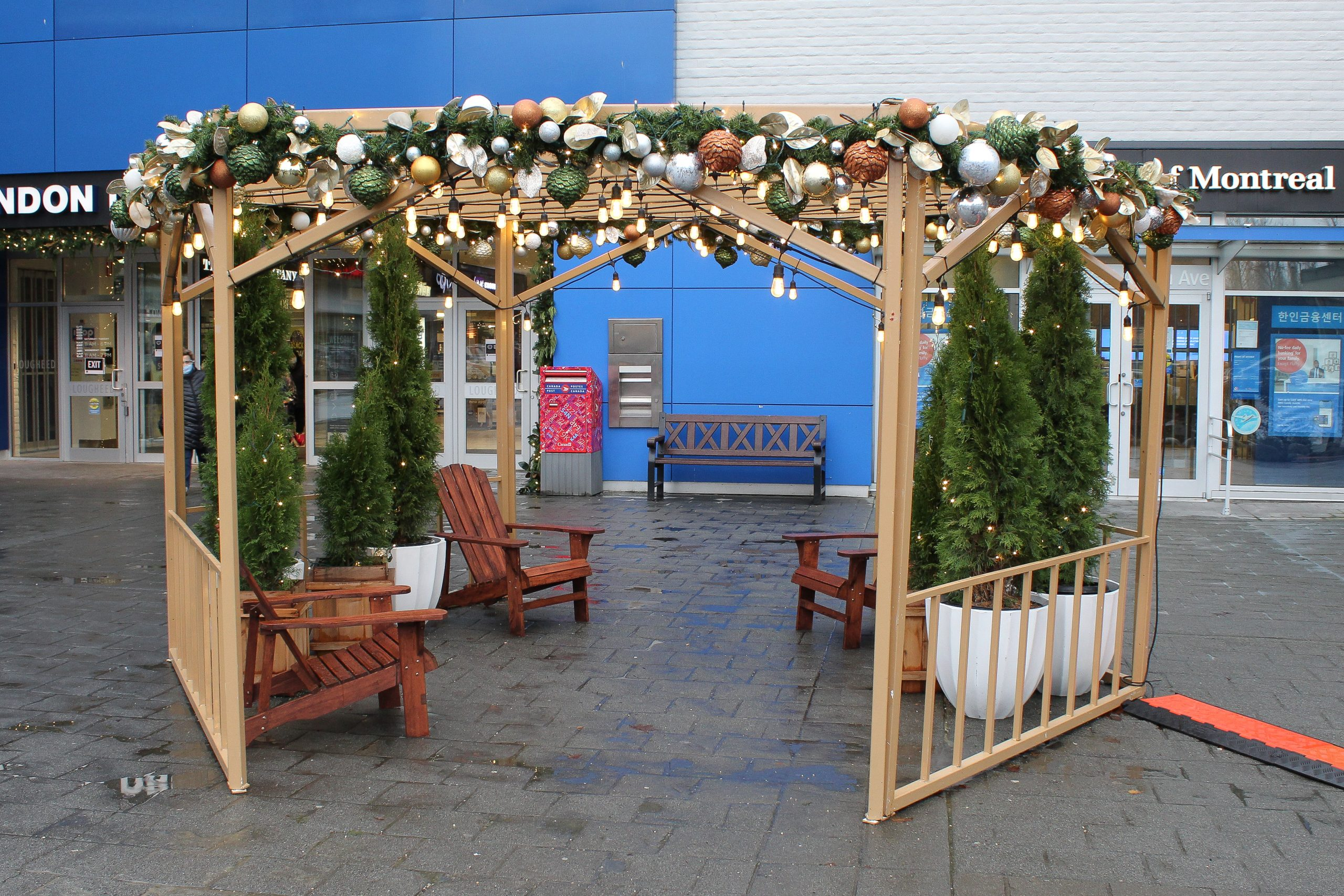 holiday decorated outdoor pergola. gold painted metal pergola with festival lights, garland, live potted cedars and adirondak seating