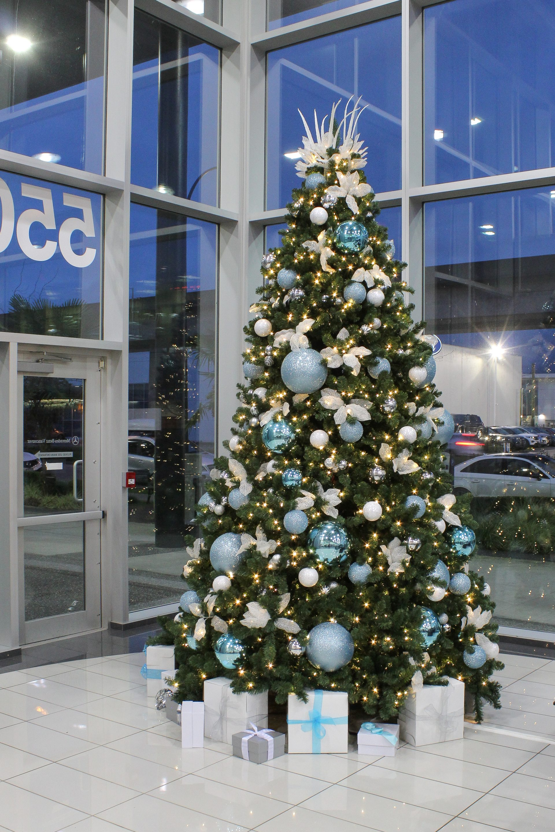 12 foot tall christmas tree decorated in white, silver and icy blue decor, present base, in car dealership