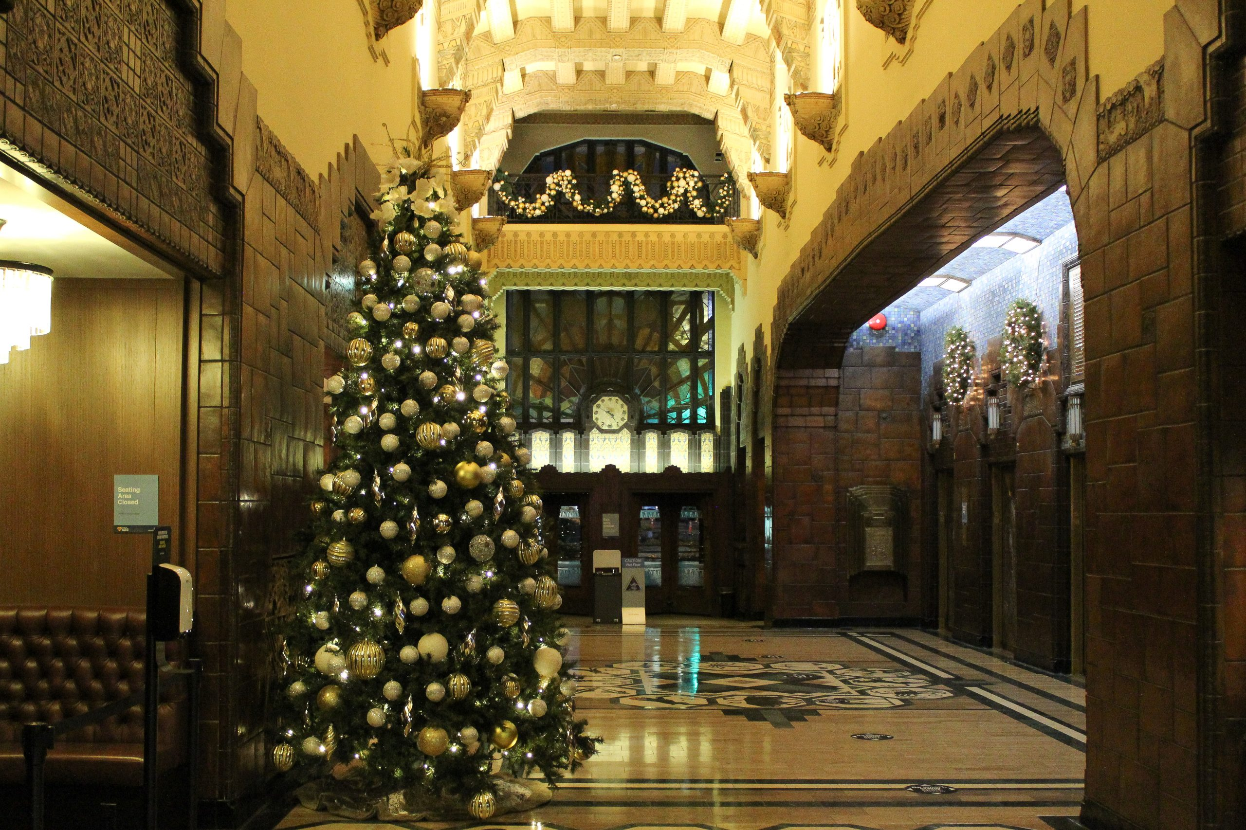 marine building christmas decor with 10' tall christmas tree decorated in white, silver and gold decor and railing garland