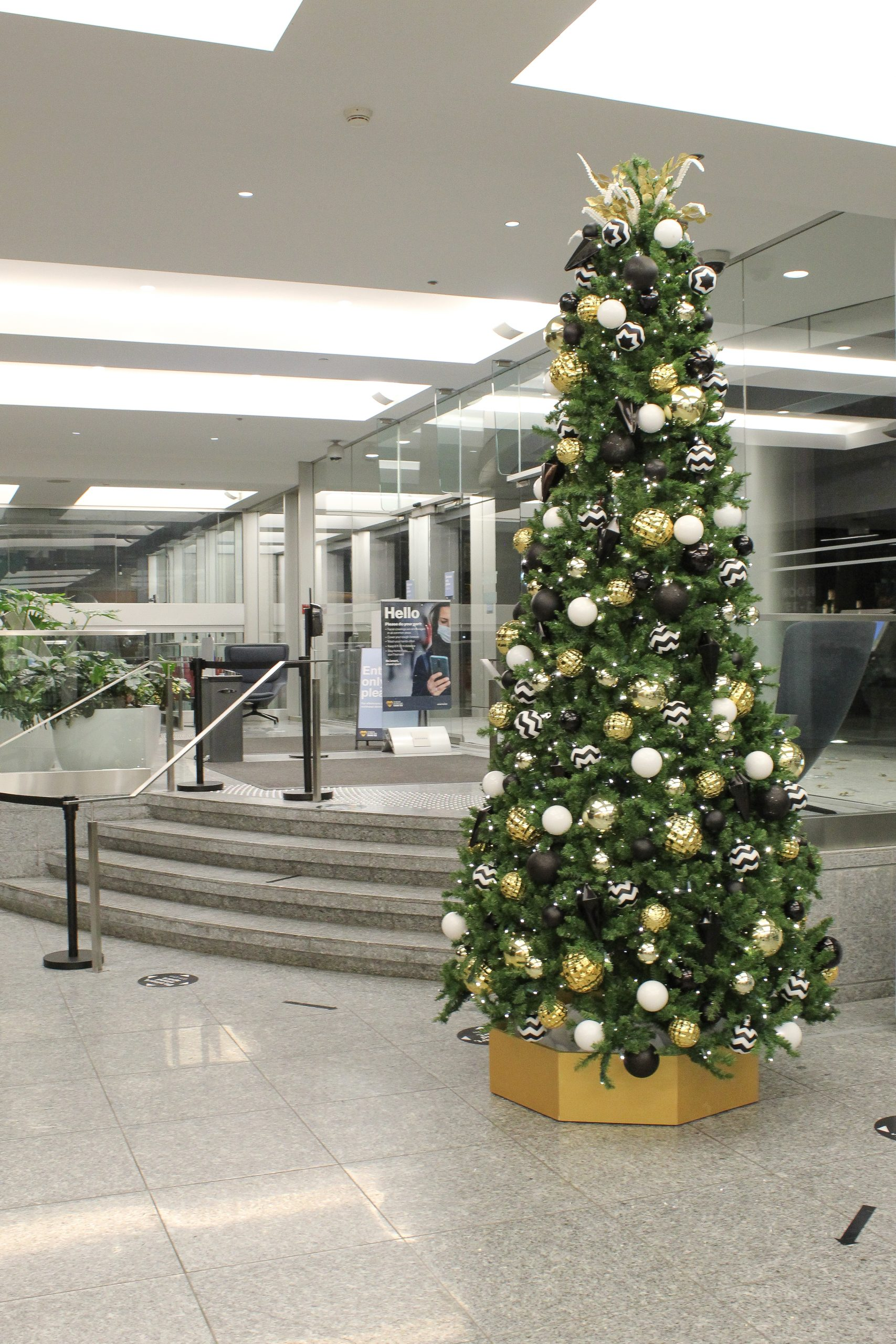12' tall artificial christmas tree with gold hexagon base decorated in black white and gold decor