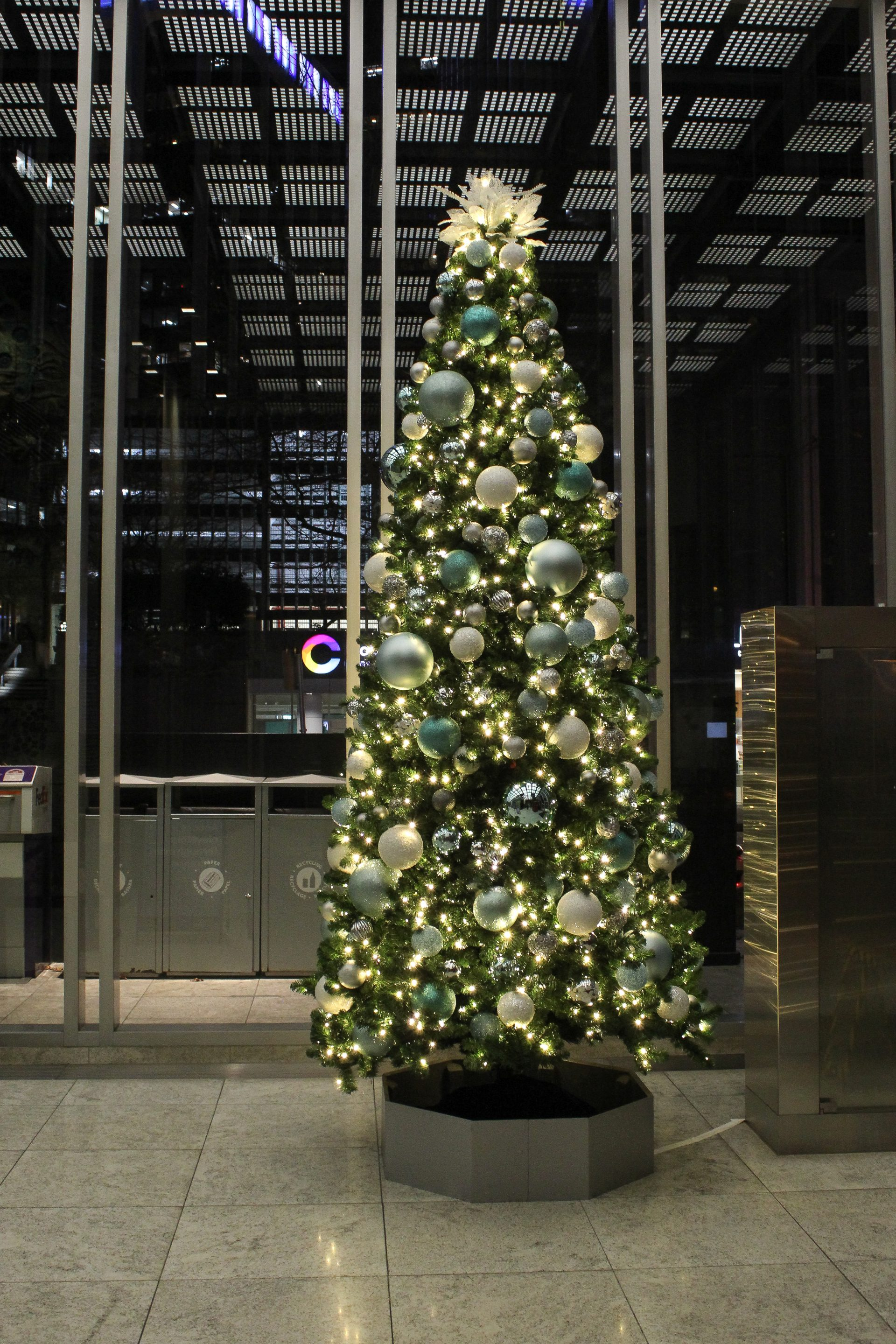 12' tall Christmas tree decorated with silver, white and teal decor inside Guinness building office loby