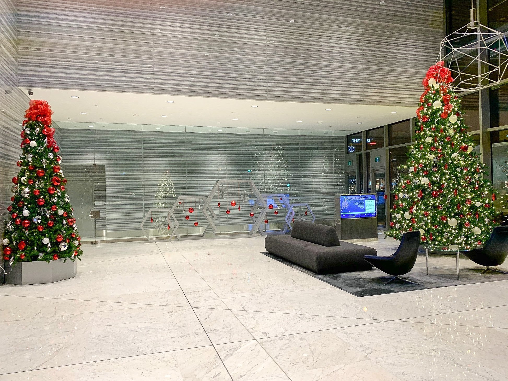 commercial office building lobby decorated in red and silver christmas trees with with hexagon tree bases and hexagon art installation