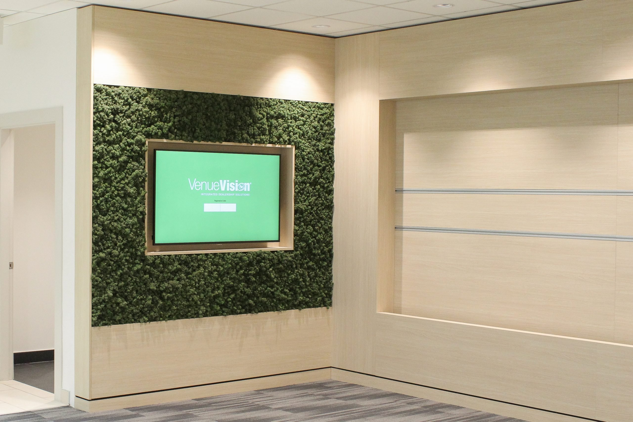 large preserved reindeer moss wall detail with inset TV in Kia car dealership