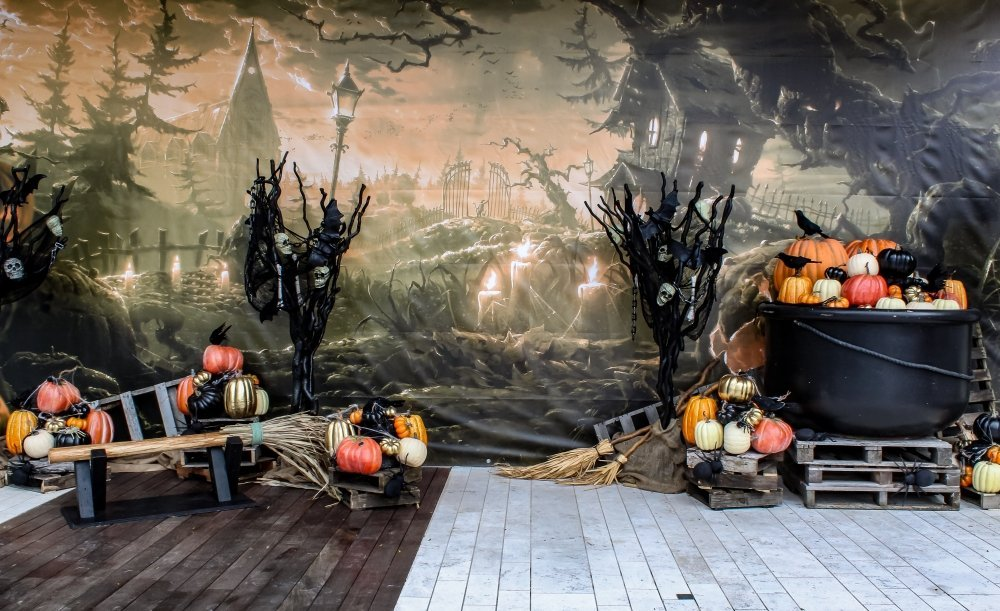halloween installation, spooky scenery backdrop, witches broom bench, cauldron, pumpkins, spooky trees and pallets.