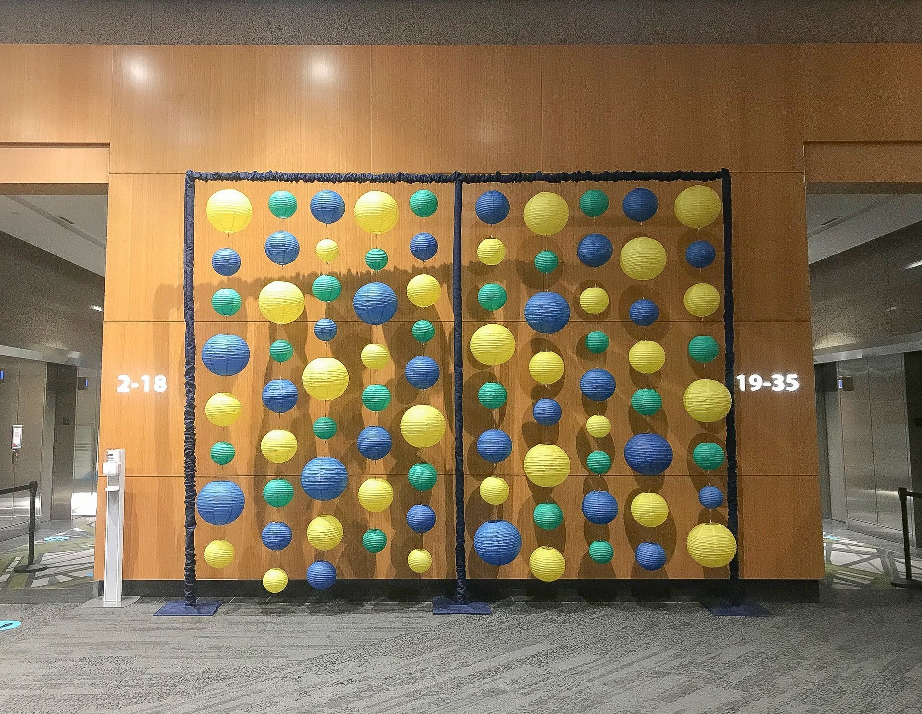 non-traditional lantern display backdrop. yellow green and blue lanterns in commercial office building lobby