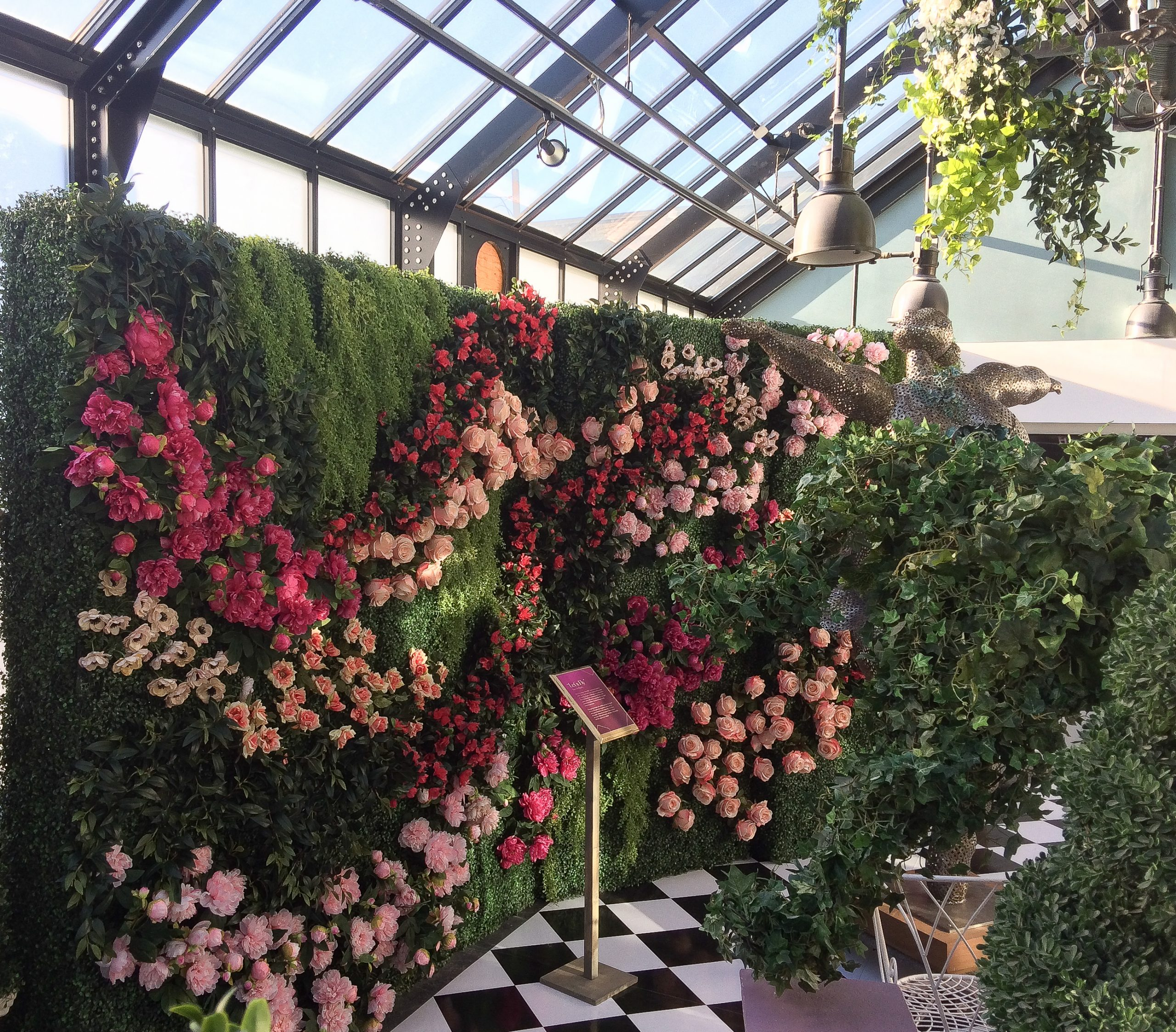 flower wall on boxwood hedge for garden party alice in wonderland theme for art of wonder