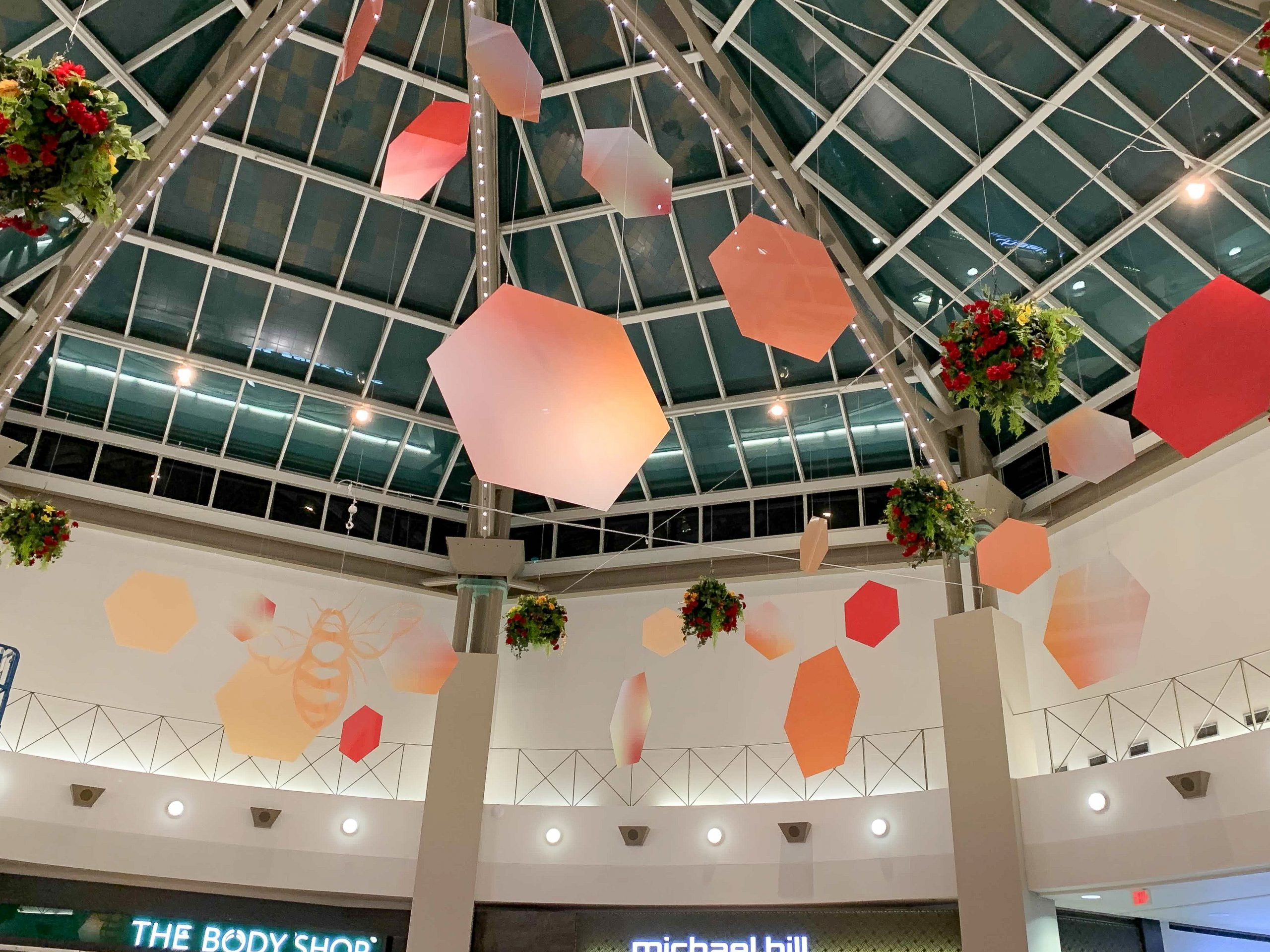 sevenoaks shopping centre bee custom display with hanging hexagons, hanging baskets and large bee cutout