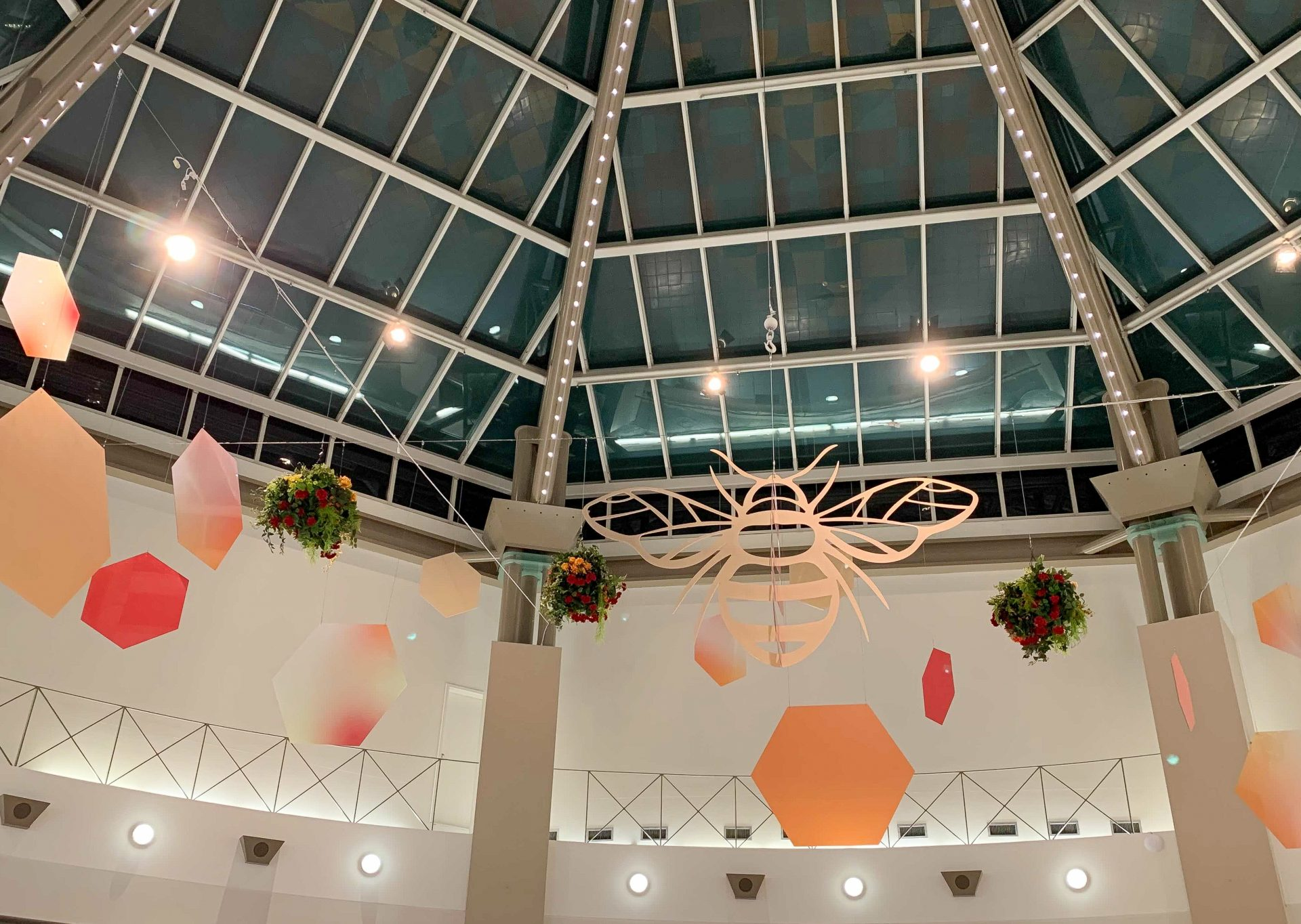 custom hanging bee display at sevenoaks mall, with hanging baskets, hexgon shapes and large bee cutout