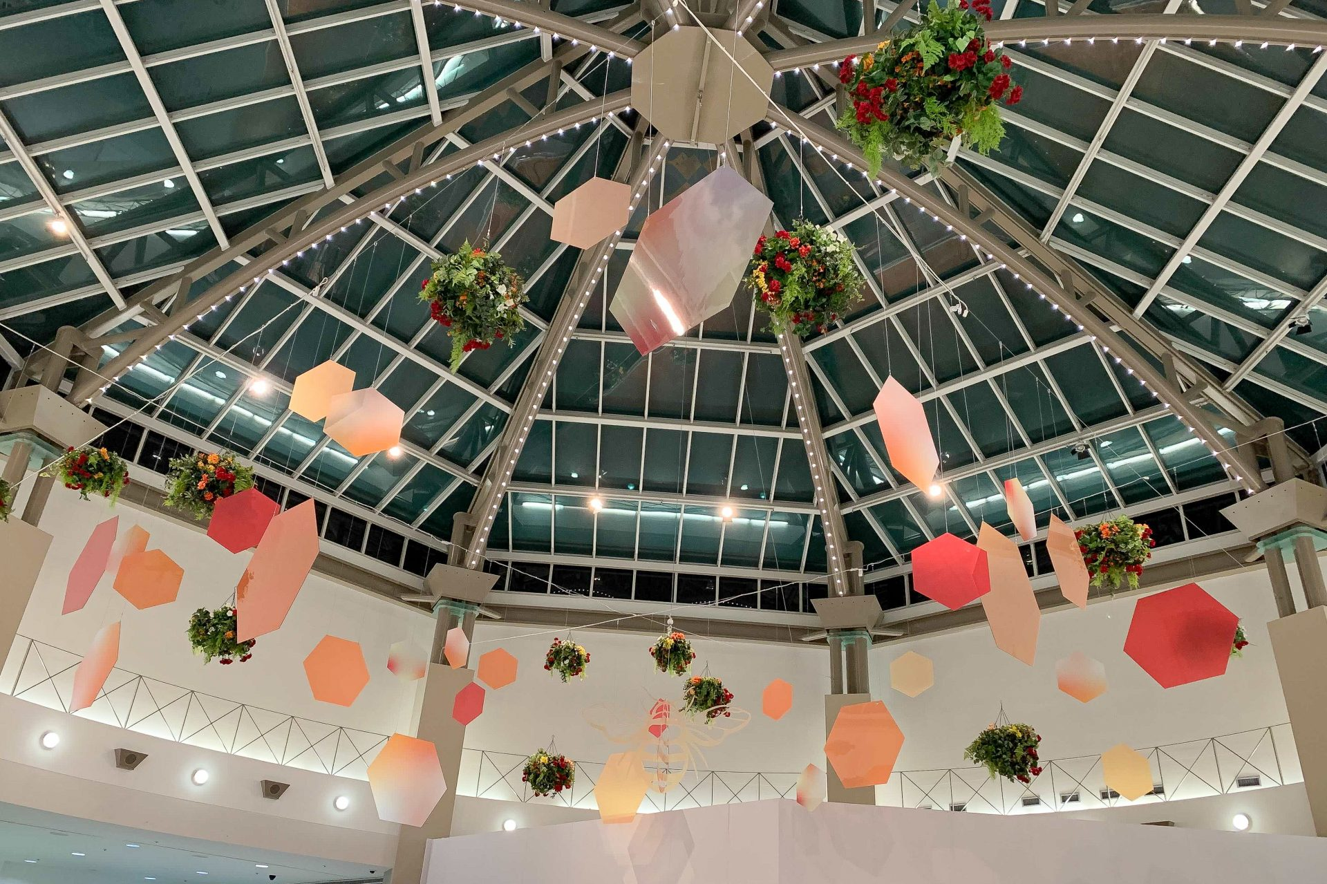 hanging bee ceiling display with various size hexagon shapes, large bee cut out and hanging baskets at sevenoaks mall