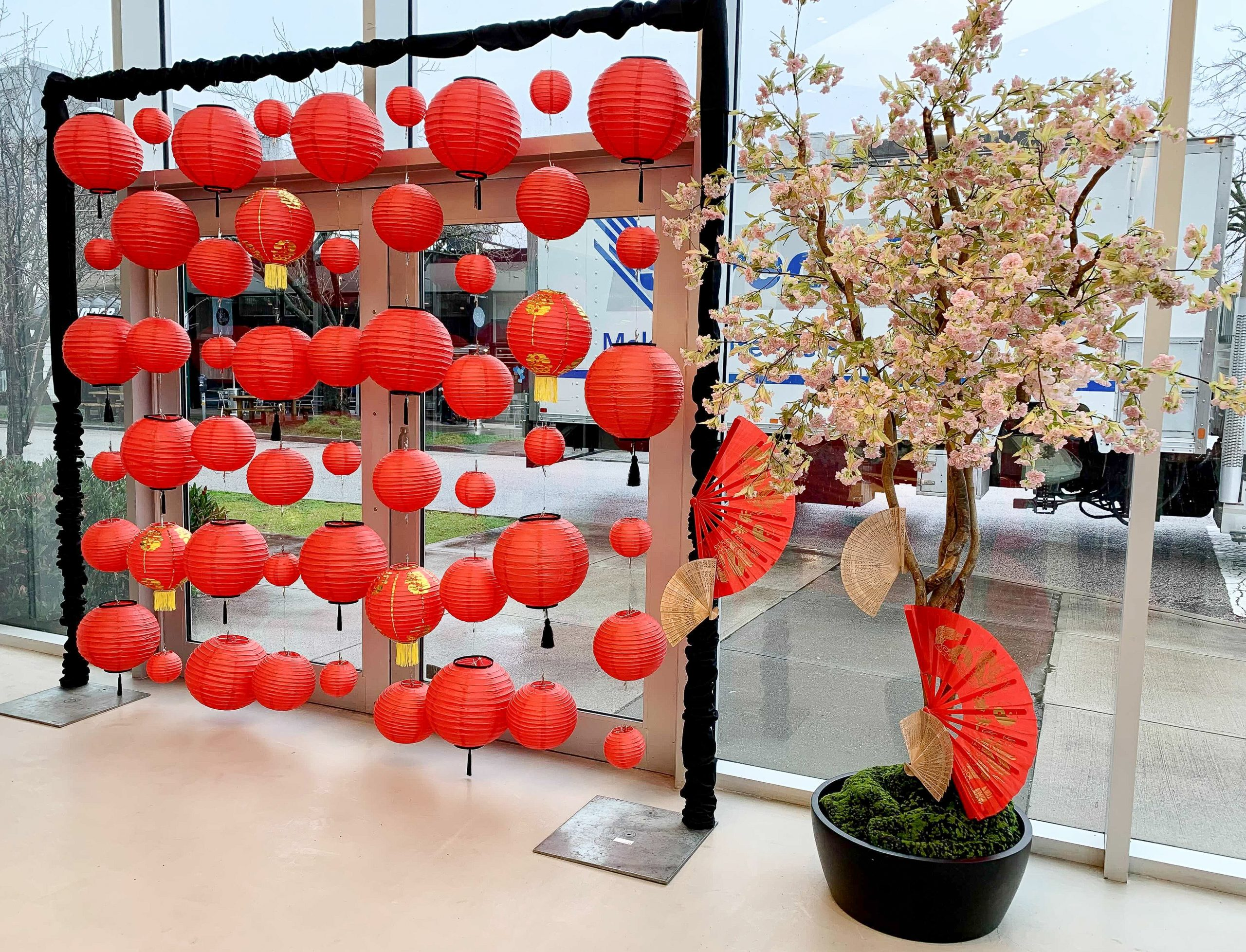 Traditional red and gold lantern display with small pink cherry blossom wishing tree in presentation centre