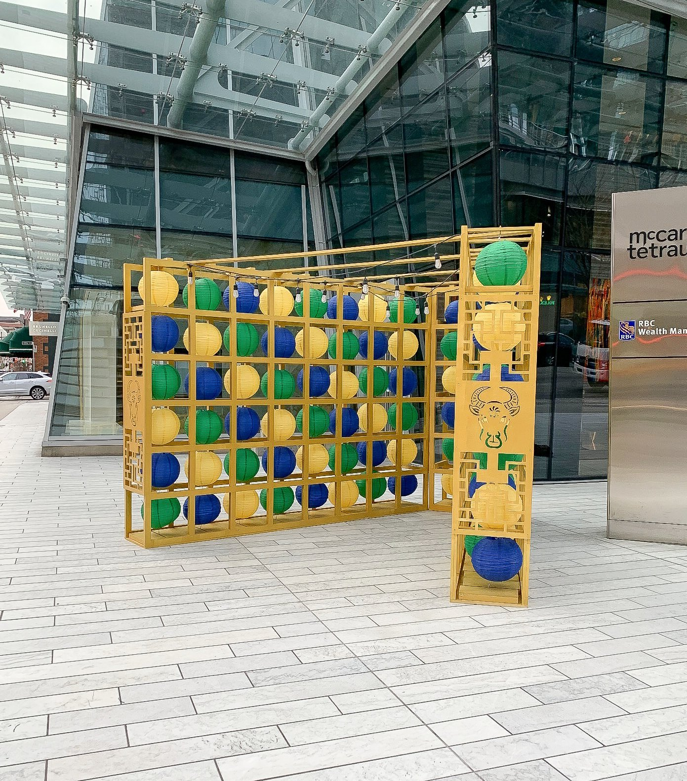 Outdoor downtown vancouver courtyard display of non-traditional yellow green and blue lanterns for lunar new year