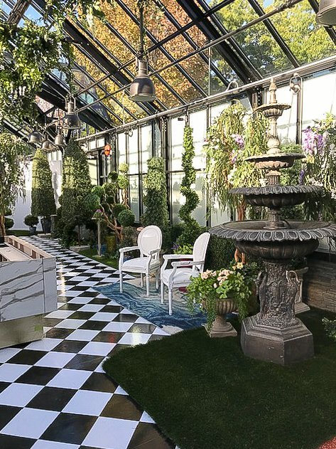 garden party alice in wonderland art of wonder, bronze fountain with lots of topiaries in a green house