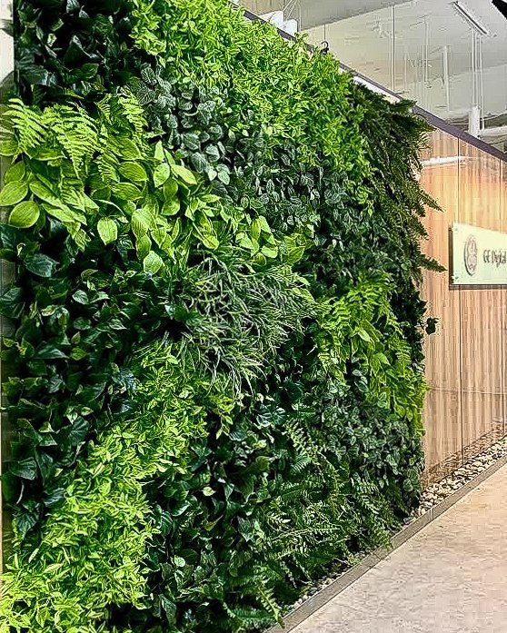 Mixed leafy artificial green wall in office lobby