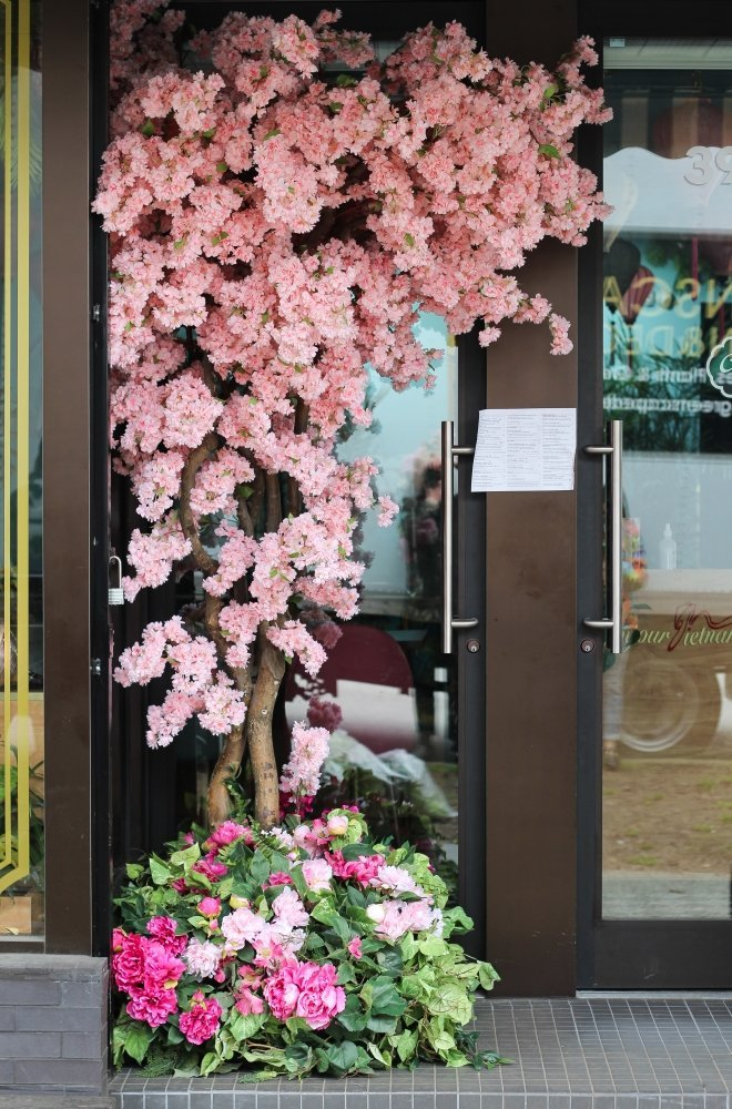 Custom pink cherry blossom tree for corner of restaurant entrance with greenery and pink flower base garden