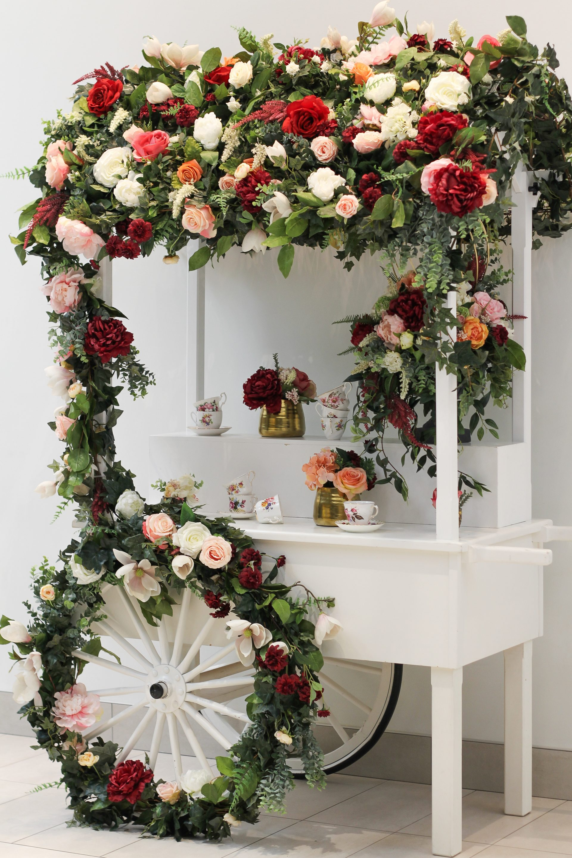 White flower cart on wheels adorned with flower wall roof covering and artificial floral details
