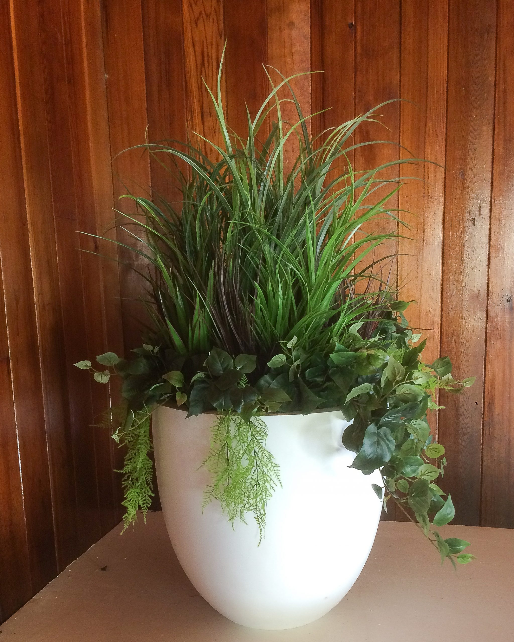 Large white round fibreglass planter with grasses and mixed greenery, wood paneling background.